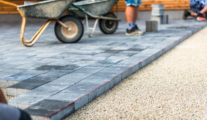 Professional bricklayers are shown installing new tiles or slabs for a sidewalk or patio on a leveled foundation base made of sand. Home improvement projects you should leave to the professionals include any structural changes that involve load-bearing walls, electricity, plumbingand concrete work.