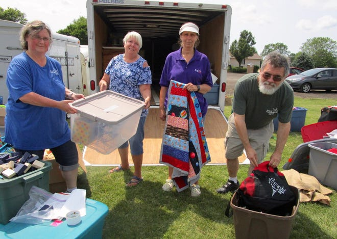 Jan DuMond, left; Judy Cooksey, both volunteers with Royal Family Kids Camp; Wendy Townsend, camp director; and her husband, Michael Townsend, take inventory of items to be used at this year's camp.