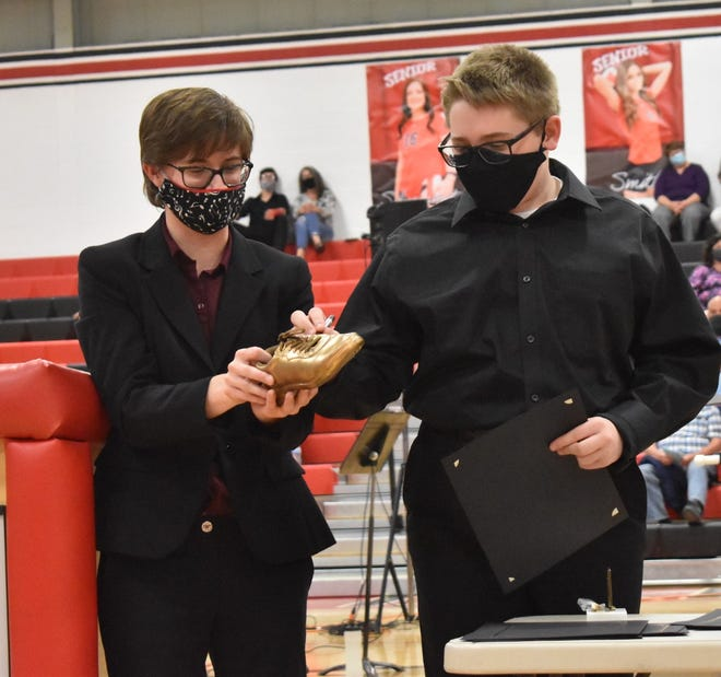Orion High School band director Lauren Heiberger, left, has Bobby Carlson, winner of the Most Improved Band member award, sign the Golden Shoe that commemorates the award.