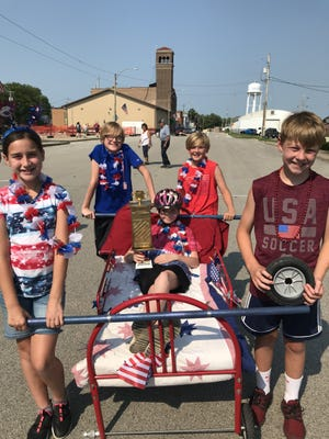 Only two teams competed in the bed races Sunday on Front Street. The winners were from left in front, Arabella Porsche, Niya Roman, (in bed holding the trophy) and Aiden Hawkins. In back from left, Randel Engels and Lucas Piester.