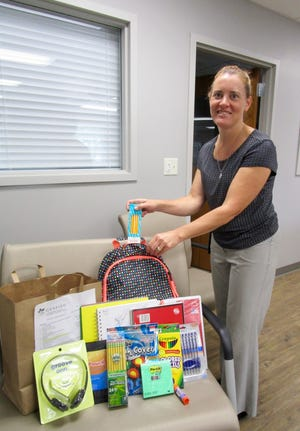 Nicole Freadhoff, interim director at the Geneseo-Atkinson Food Pantry, is shown with some of the school supplies to be distributed Aug. 5-6 to students in the Geneseo School District.