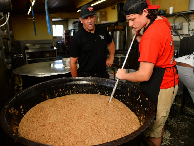 This is Midway BBQ in Buffalo. Owner Jay Allen, left, and Caden Inman prepare the pot of beef hash.