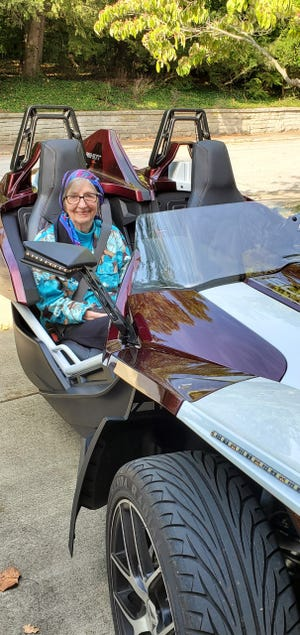 Gayle Cook rides in Teresa Hull's Slingshot. Hull is Cook's assistant.