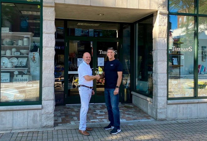 Joe Nelis (left) and Jeff Teerman pose for a photo after reaching a lease agreement for Nelis' Dutch Village's storefront downtown.