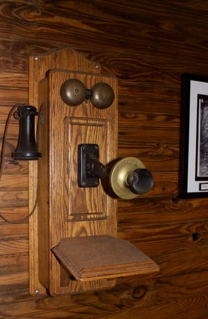 """A circa-1915 wall-mounted telephone consisting of a wooden box. It was operated by two dry-cell batteries, two bells, a crank and a separate mouthpiece from the """"horn,"""" which hung from a hook when not in use. Anything but portable, this device featured no camera nor caller-ID, mobile browser."""