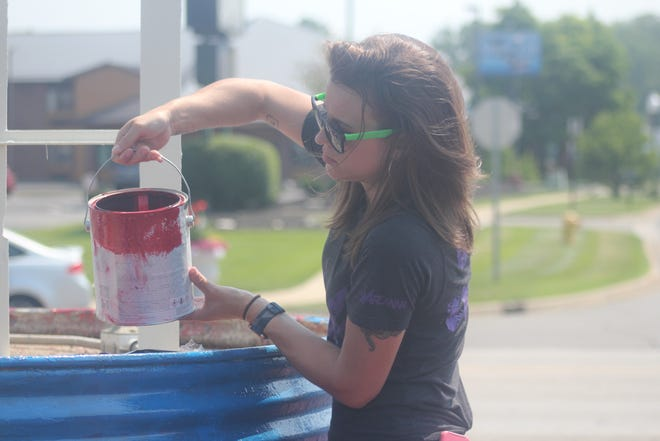 Arcanna Director of Human Resources Jackie Cremer paints one of the four towers at the entrance to the Ionia Free Fair, 317 S. Dexter St., in Ionia on Tuesday, July 6.