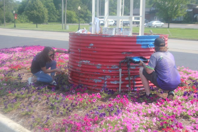 Arcanna Director of Human Resources Jackie Cremer (left) and Brand Representative Jordan Vergeson paint one of the four towers at the entrance to the Ionia Free Fair, 317 S. Dexter St., in Ionia on Tuesday, July 6.