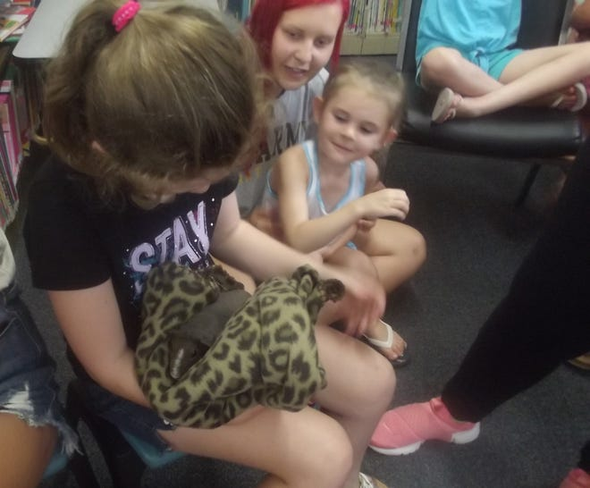 A young girl cradles a guinea pig while others look on.