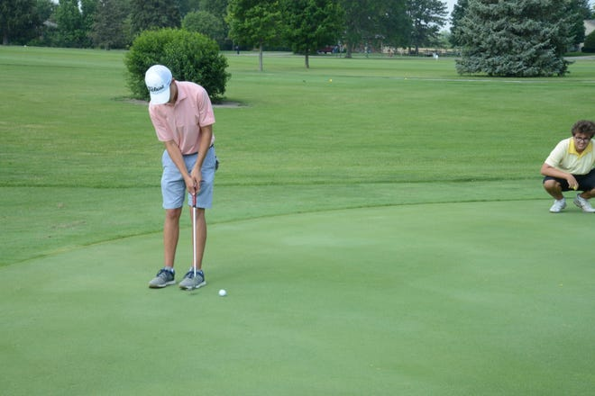 Cale Piedmonte-Lang putts while Justin Lauer Jr. of Canton (right) looks on Tuesday during the opening round of the La-Z-Boy Junior Open Tuesday. Piedmonte-Lang leads Lauer by a stroke in the 17-19 boys division.