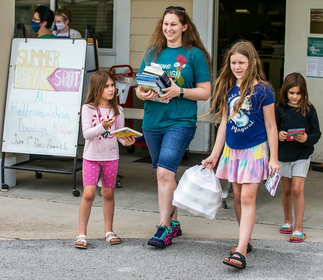 """Natalie Lejkowski, 6, left, walks with her mom, Lori, and sisters Elizabeth, 9, second from right, and her twin Makalie, 6, right, after the family found out about the Summer BreakSpot Grab & Go dinners at the Belleview Public Library Tuesday evening.  """"I didn't plan this. I just found out about it. It makes it where I don't have to cook tonight,"""" Lejkowski said."""