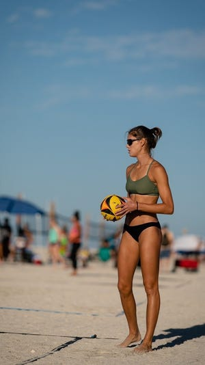 Christina Matthews prepares to serve during a game of beach volleyball. Her professional career was cut short by a serious ACL injury in 2018.