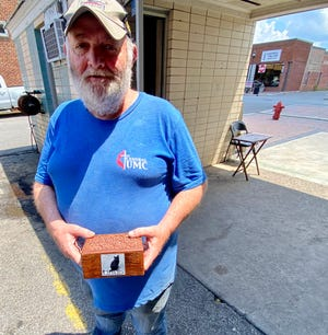 Tony Hamrick holds the remains of Blackie at AA United Cab Company in Shelby