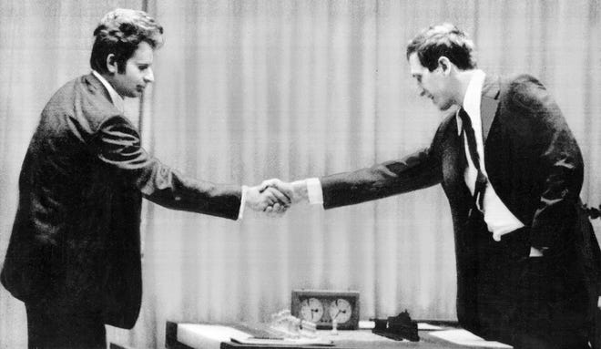 Russian chess master Boris Spassky, left, shakes hands with Bobby Fischer at the Laugardalsholl Hall in Reykjavik, Iceland, on July 11, 1972. Spassky made the first move before Fischer arrived. (AP Photo)