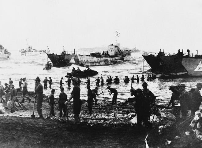 Allied soldiers stand waist deep in water as they leave landing craft during the first day of the Sicilian invasion on  July 10, 1943. In the foreground, soldiers prepare beach roads.