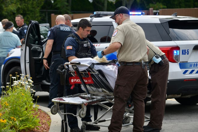 Suspect in stolen vehicle case is taken away in an ambulance.