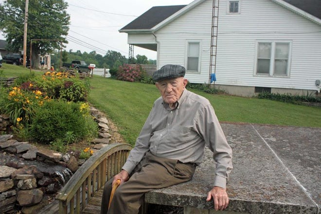 Clarence Hall sits by the waterfall garden he built a few years ago.