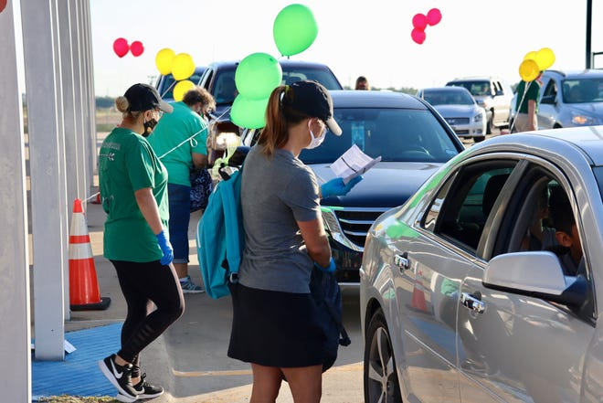 Waxahachie ISD volunteers assist families with school supplies during a socially distant back-to-school event last year. The school district has set its Operation First Day of School for July 31 at Clift Elementary School.