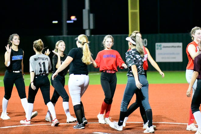 Ellis County All-Star softball players congratulate one another at the end of last Wednesday's inaugural All-Star Softball Game at Waxahachie High School. The East All-Stars defeated the West, 5-0.