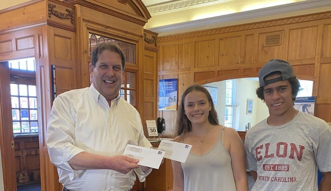 Dan Taylor, Scituate Chamber treasurer and manager at Rockland Trust, Scituate presents Natalie Moore and Mathew Melanson with scholarship checks.