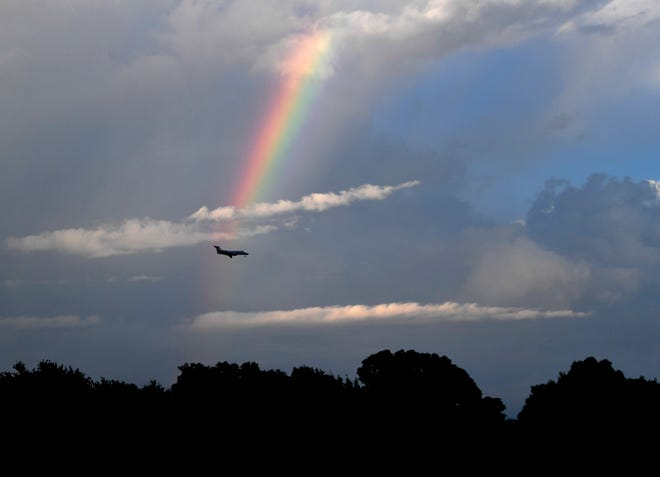 An aircraft passes by a rainbow as it makes an approach to Abilene Regional Airport just past Nelson Park lake and the Abilene Zoo on Monday.