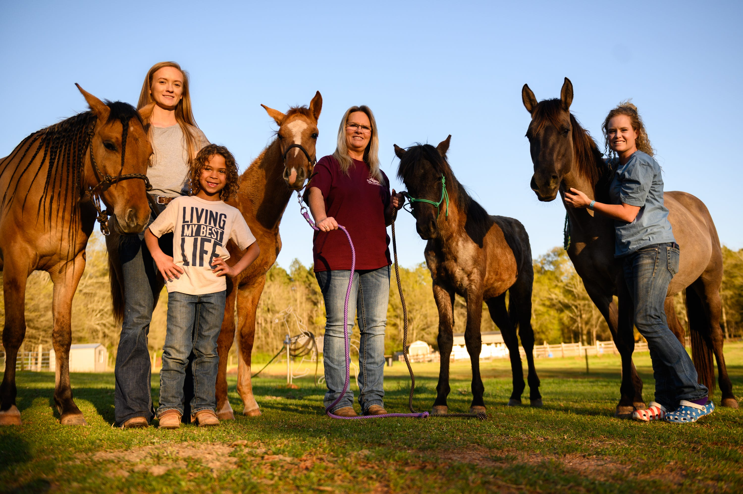 Laikyn Hawk, Kash Griffin, Tammy Coppage and Molly Simpson pose with their Marsh Tacky horses Estelita, Blue Jeans, Cricket and Sprite on March 29, 2021. The Marsh Tacky is believed to be a descendant of Spanish horses that evolved to have unique adaptations to the marshy low country conditions.