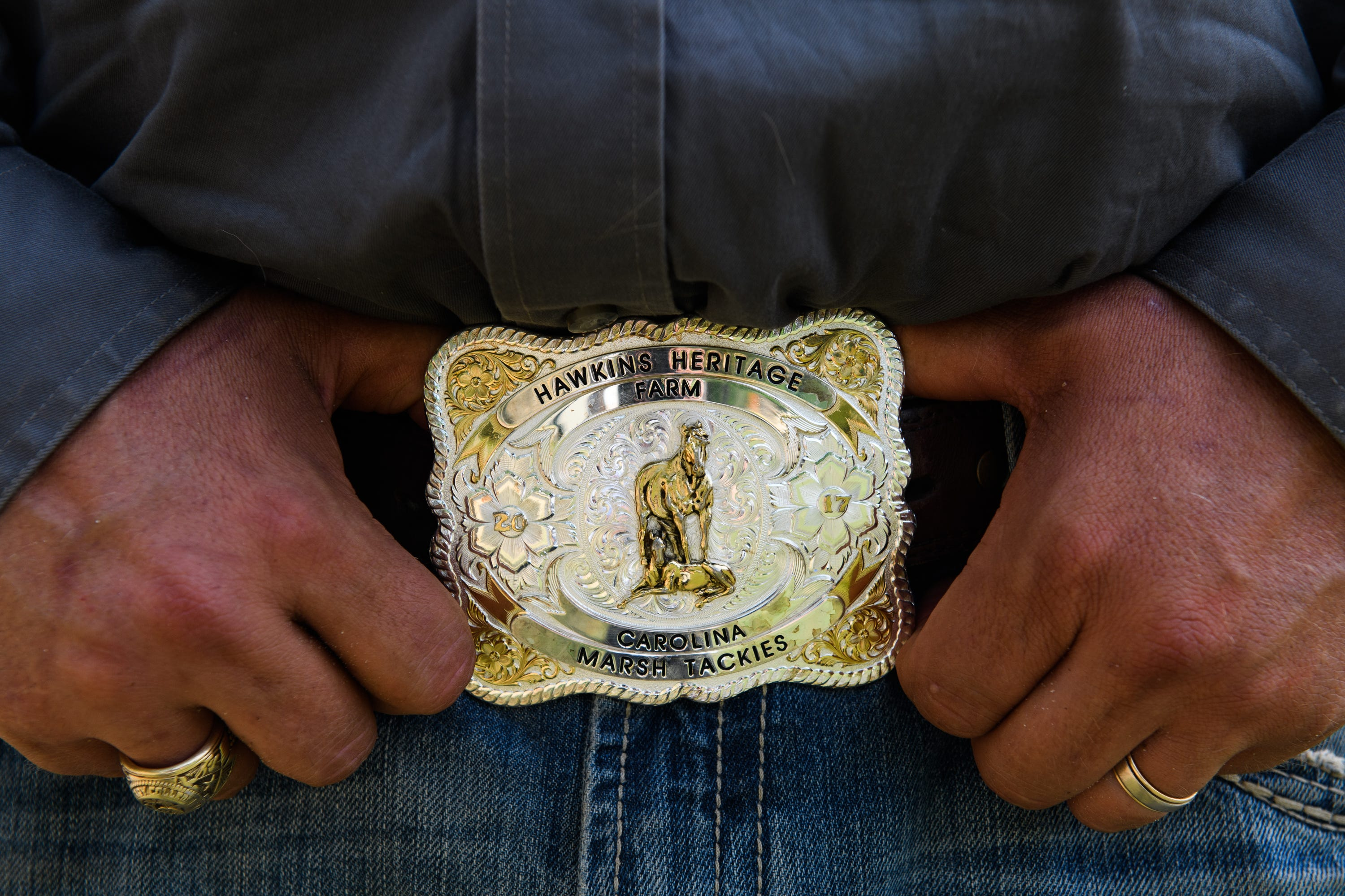 Shannon Hawkins shows off his Hawkins Heritage Farm belt buckle, featuring a Marsh Tacky horse, as he poses for a portrait on April 15, 2021.