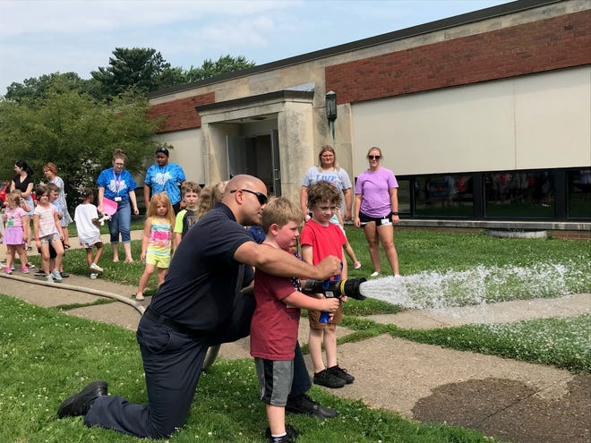 Mansfield fire Lt. Steve McKay teaches each child at Mansfield Safety Town Tuesday how to hold a fire hose correctly outside the Spanish Immersion School.