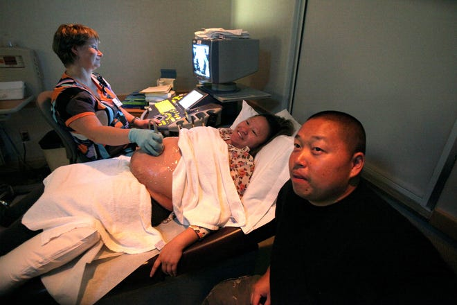 Perinatal sonographer Rita Siudak shows Kalia Yang and Andy Moua an ultrasound image of their twins on a monitor above them at Wheaton Franciscan-St. Joseph's prenatal assessment center. Yang has learned from her doctor and social worker about having a healthy pregnancy.