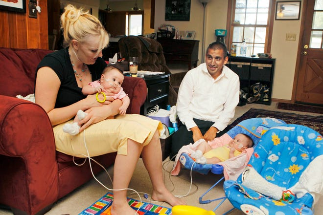 Laurie Navarro holds daughter Emilia, or Millie, while Santiago Navarro sits by her twin sister, Simona, on Sept. 1 at the couple's Fox Point home. The girls were born early because of heart complications and weighed less than 1 1/2 pounds each.