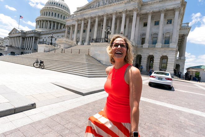 Sen. Kyrsten Sinema, D-Ariz., smiles as she returns to the Capitol after a meeting with President Joe Biden at the White House in Washington, Thursday, June 24, 2021. A bipartisan group of lawmakers have negotiated a plan to pay for an estimated $1 trillion compromise plan. (AP Photo/Alex Brandon)