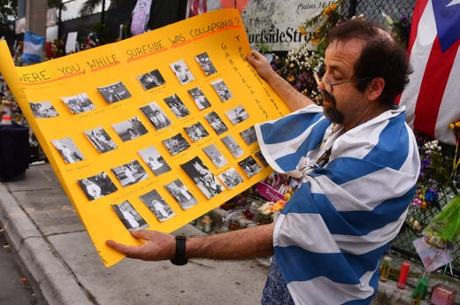 Bernardo Camou Font, a mathematics professor from Uruguay, wrapped in his country's flag, came to the Surfside Wall of Hope and Memorial with a large yellow poster filled with photos of his sister on July 6, 2021. His sister, Gabriela Camou Font died in the collapse of the Champlain Towers South condominium.