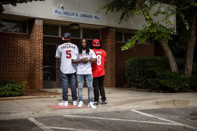 Kawanis Sutton 26, who uses the stage name Yung Petro, poses for a photo with Darius Brightwell, left, and Dereion Smith at the old Nellie B Library on June 10, 2021.