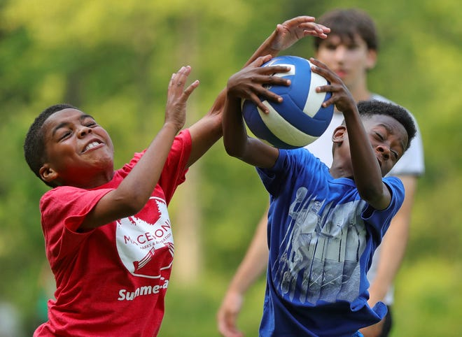 Christopher Lawler, 10, left, and Deonte Terrell, 10, right, play catch during the Macedonia Summer Day Camp, Wednesday, July 7, 2021, in Macedonia, Ohio.