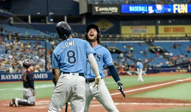 Tampa Bay's Brett Phillips celebrates with Brandon Lowe (8) after Phillips hit a solo home run off Cleveland reliever Trevor Stephan during the sixth inning in the first game of a doubleheader Wednesday, July 7, 2021, in St. Petersburg, Fla.(AP Photo/Steve Nesius)