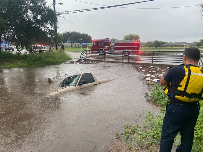 First responders are on North Stadium with a vehicle submerged in water.