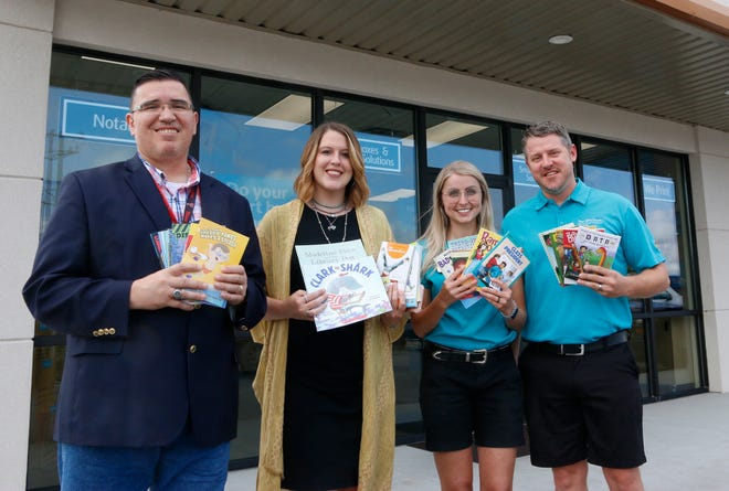 From left, Dione White, Angela Baker, Rachel Russell and Jamison Russell hold some of the children's books donated to the Center of Life Resources through the partnership between the UPS Store and the Toys for Tots Literacy Program.