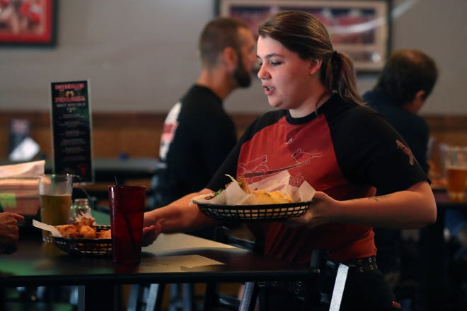 Jennifer Griffin serves an order to a customer July 2 at Scoreboard Pub & Grill in Delaware.