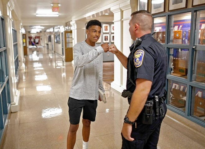 Worthington Division of Police officer Sean Ord greets Thomas Worthington High School 2018-19 senior Noah Tennant on Aug. 16, 2018. Worthington Schools' school-resource-officer program was discontinued after two years by the school boardin 2020. A student recently started a petition drive to bring back the SROs.