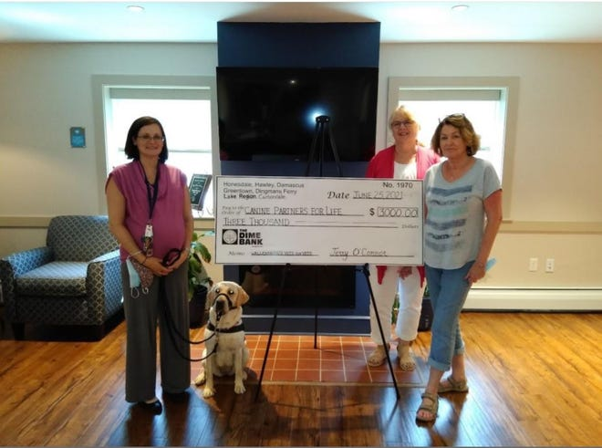 Wallenpaupack Vets for Vets has presented a check for $3,000.00 to Canine Partners for the sponsorship of a service dog for a veteran.  Kristin Downie, Vets for Vets, is to the left of the check standing with the service dog. Debbie Marks is to the rear of the check and Janet Sellitti is in front of her.  / Contributed image