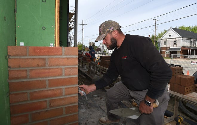 Owen Zellefrow, a mason with Randolph Masonry of Erie, lays brick on May 6 at an apartment building under construction at 331 E. 12th St. in Erie. Skilled construction workers are in high demand.