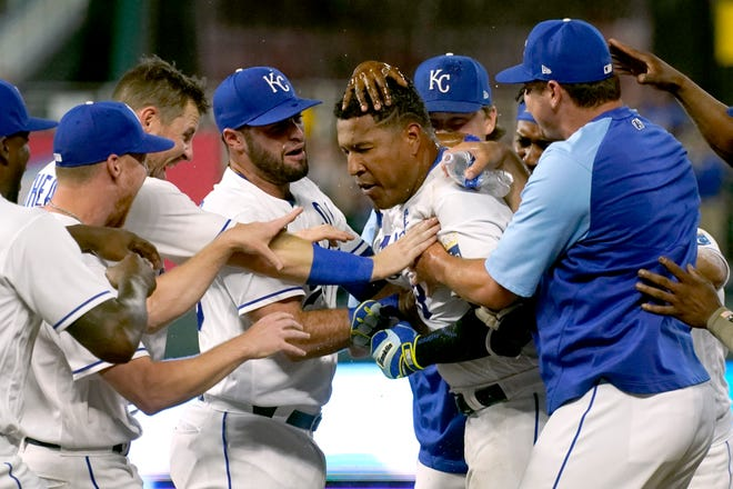 Kansas City Royals' Salvador Perez, right center, is mobbed by teammates after hitting a walk-off single in the ninth inning of Tuesday's game against the Cincinnati Reds at Kauffman Stadium. The Royals rallied from a 6-1 deficit with six runs in the final two innings, including four in the ninth, to claim a 7-6 win.