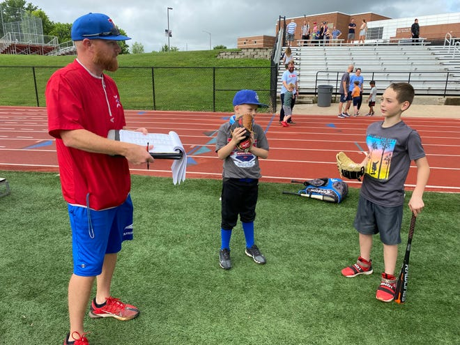 Truman High School baseball coach Corey Lathrom visits with campers Winston Hystead, middle, and Edward Parker Jr. The camp attracted 59 youngsters from the third through eighth grade.