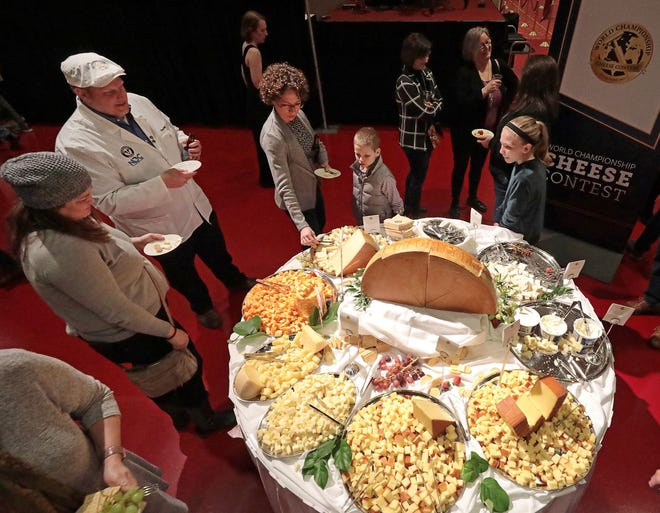 In this March 5, 2020 file photo, visitors to the Cheese Champion event of the World Championship Cheese Contest sample offerings from an array of international producers during the gathering at Monona Terrace in Madison, Wis.