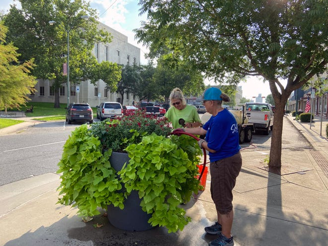 City of Sherman employees Mary Schillerwein and Tracy Renfro work on a planter located at the corner of Crockett and Lamar Streets in downtown Sherman.