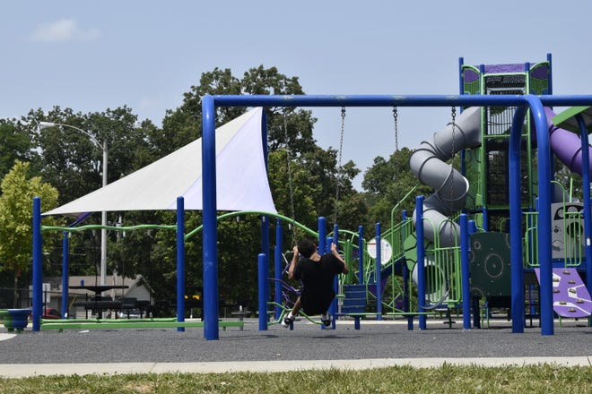 A child swings Tuesday afternoon at the Crestmont Park playground on the northwest side of Bloomington. Two shooting incidents have happened at the park over the past week.