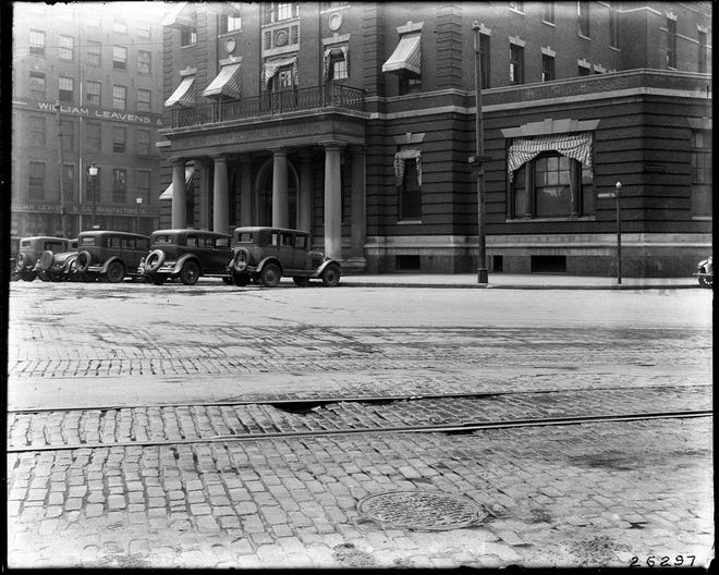 Cars are parked in front of the Boston City Hospital Relief Station in Haymarket Square as seen in May 1931. On the left side of the image, the William Leavens & Company furniture manufacturers can be seen on Canal Street. Learn more from Digital Commonwealth at www.digitalcommonwealth.org.
