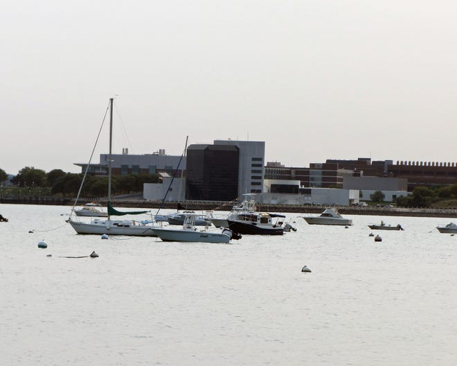 Boats are moored off the South Boston beaches with the JFK Library in Dorchester on the other side of the bay.