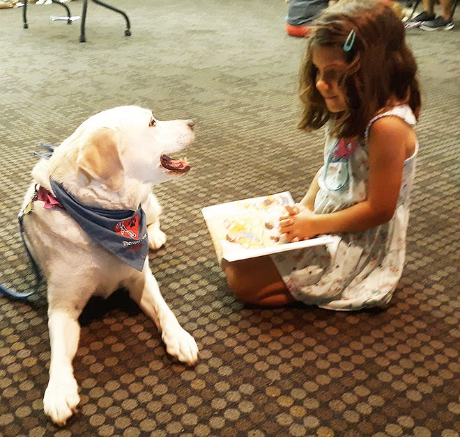 Morgan Bedard reads to Angel, who is owned by Rhonda York, during the Read to a Dog activity Wednesday at the Leavenworth Public Library.