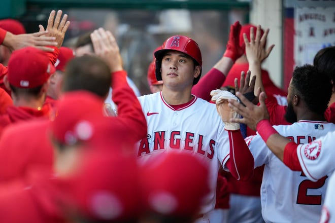 Los Angeles Angels' Shohei Ohtani celebrates in the dugout after scoring off of a home run hit by Max Stassi during the first inning of a baseball game on July 6, 2021, in Anaheim, Calif.