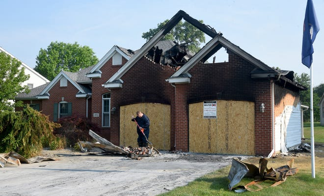 Monroe Township Fire Department Captain/Fire Inspector Calvin Schmitt inspects the damage after a fire ravaged a home in the Carrington Farms subdivision in Monroe Saturday night.